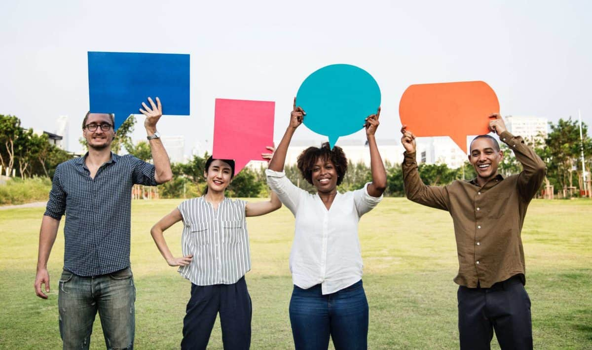 People holding up paper speech bubbles